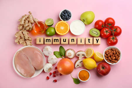 Set of natural products and cubes with word Immunity on pink background, flat lay