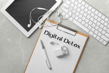 Flat lay composition of clipboard with words DIGITAL DETOX on light grey marble background