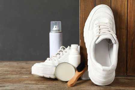 Composition with stylish footwear and shoe care accessories on wooden background Stock Photo
