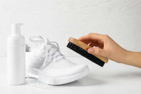 Woman cleaning stylish footwear on white background, closeup. Shoe care accessories