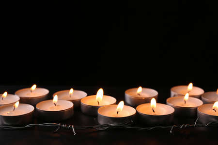 Burning candles and barbed wire on black background, space for text. Holocaust memory day