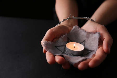 Woman tied with barbed wire holding star of David and burning candle on black background, closeup. Holocaust memory day