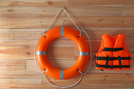 Orange life jacket and lifebuoy on  wooden background. Rescue equipment Standard-Bild