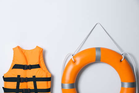 Orange life jacket and lifebuoy on light background. Rescue equipment