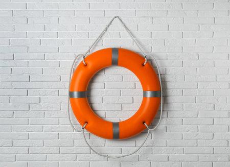 Orange lifebuoy on white brick wall. Rescue equipment