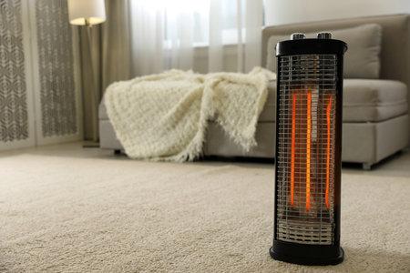 Modern electric halogen heater on floor in living room interior Banque d'images