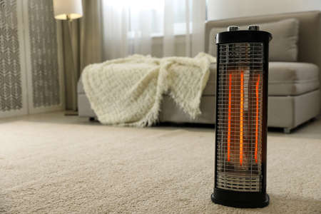 Modern electric halogen heater on floor in living room interior