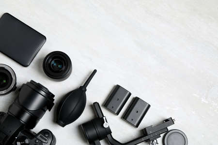 Camera and video production equipment on light background, flat lay. Space for text