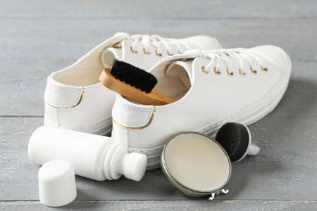 Composition with stylish footwear and shoe care accessories on grey wooden background