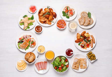 Buffet service. Frame of different dishes on white wooden table, space for text Stock Photo