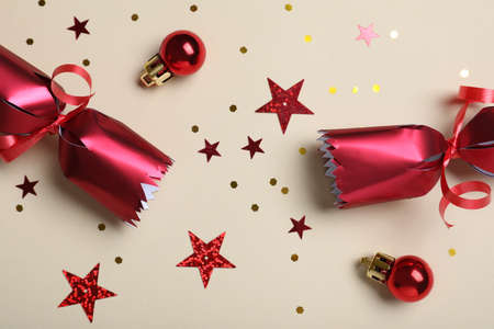 Open red Christmas cracker and decorations with shiny confetti on beige background, flat lay