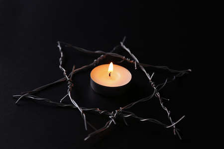 Burning candle and star of David made with barbed wire on black background. Holocaust memory day Stockfoto