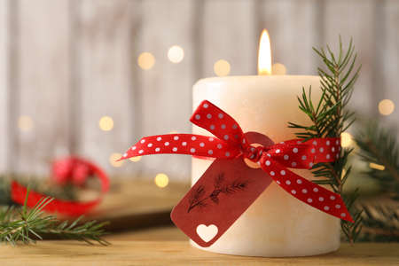 Burning candle with pinecone scent on wooden table, closeup. Space for text