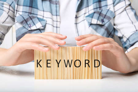 Woman demonstrating blocks with word KEYWORD at white table, closeup