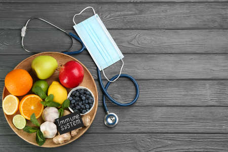 Card with phrase Immunity System, medical items and fresh products on grey wooden table, flat lay. Space for text Stok Fotoğraf