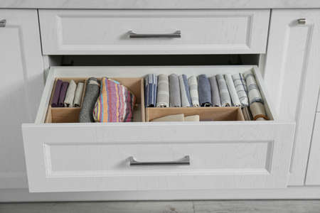 Open drawer with different textiles in kitchen