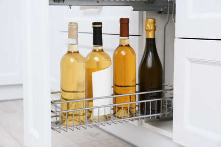 Open drawer with wine bottles in kitchen