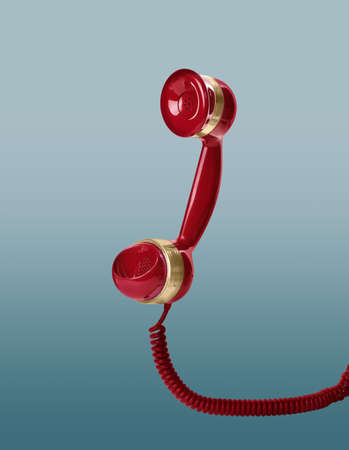 Handset of vintage red corded telephone flying in air on light blue background