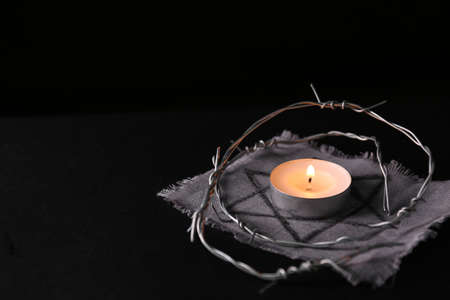 Fabric with star of David, barbed wire and burning candle on black background, space for text. memory day Stockfoto