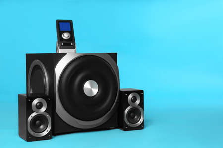 Modern powerful audio speaker system with remote on light blue background, space for text