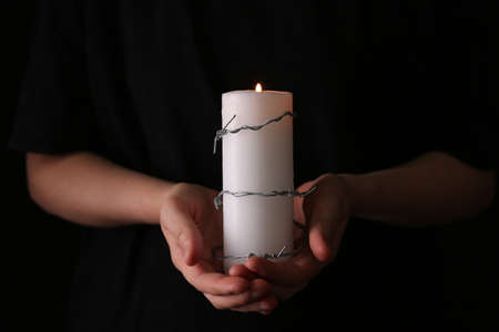 Woman holding candle with barbed wire on black background, closeup. memory day