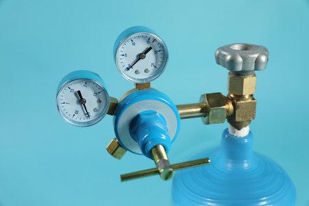 Pressure gauge of medical oxygen tank on light blue background, closeup
