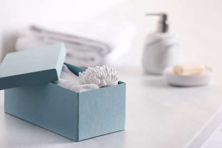 Cotton buds and pads in box on white table indoors