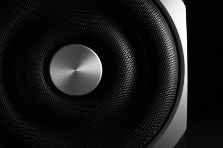 Modern subwoofer on black background, closeup. Powerful audio speaker