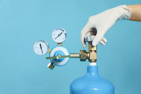 Medical worker checking oxygen tank on light blue background, closeup Reklamní fotografie