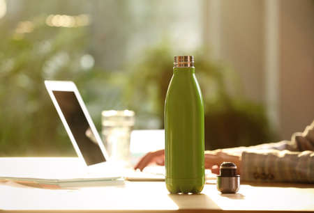 Woman working at table in modern office, focus on green thermo bottle. Space for text