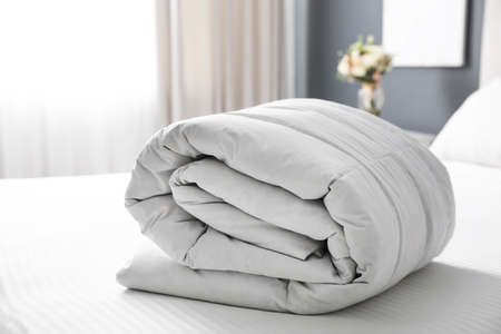 Soft folded blanket on bed at home Stock Photo