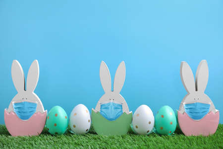 Easter bunny figures in protective masks and dyed eggs on green grass against light blue background