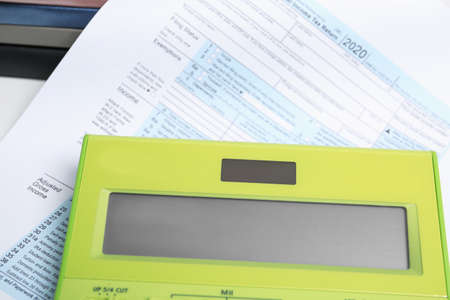 Calculator and document on table, closeup view. Tax accounting