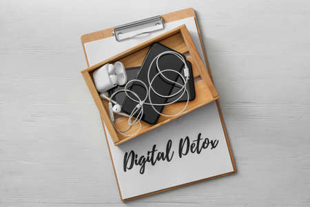 Different gadgets in crate and clipboard with words DIGITAL DETOX on white wooden background, top view