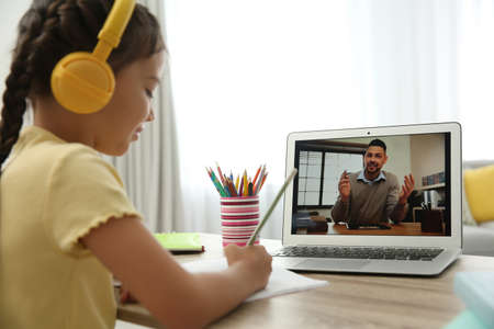 Distance learning, studying at home. Girl having online school lesson with teacher during quarantine and lockdown due to pandemic Zdjęcie Seryjne