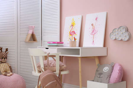 Stationery and pictures on white table in children's room. Interior design