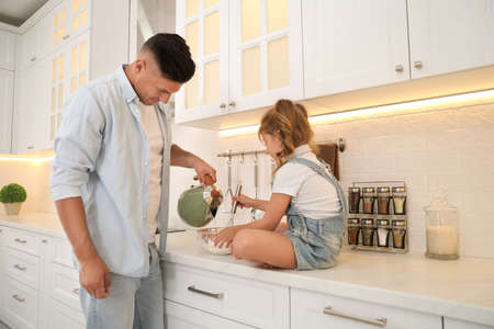 Little girl with her father cooking together in modern kitchen
