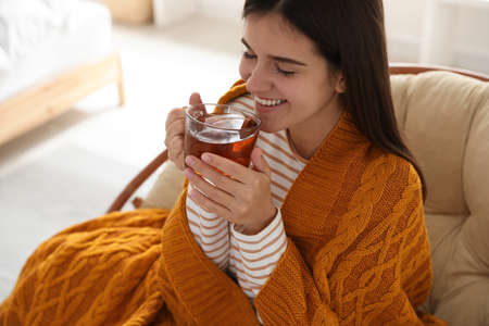 Woman covered with warm orange plaid enjoying hot drink at home