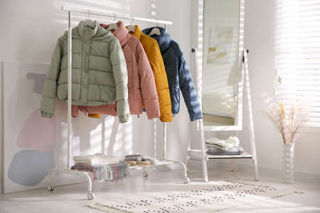 Different warm jackets on rack in stylish room interior Foto de archivo