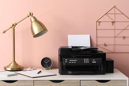 New modern printer with paper on white table at workplace