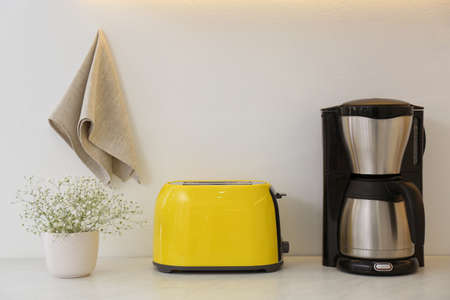 Modern toaster, coffee machine and flowers on counter in kitchen Banque d'images