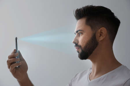 Young man unlocking smartphone with facial scanner on grey background. Biometric verification
