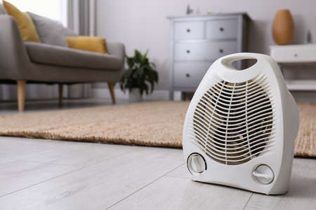 Modern electric fan heater on floor at home. Space for text