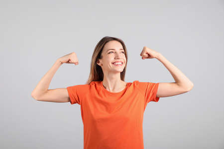 Strong woman as symbol of girl power on light grey background. 8 March concept