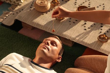 Man at crystal healing session indoors, closeup
