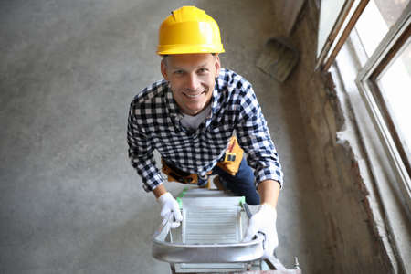 Professional constructor on ladder in old building, above view