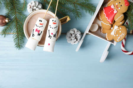 Flat lay composition with funny snowmen made of marshmallows on light blue wooden table. Space for text
