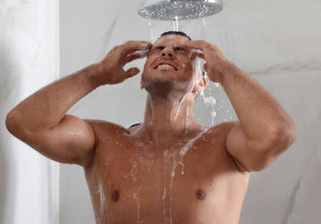 Handsome man washing hair in shower at home Stock fotó