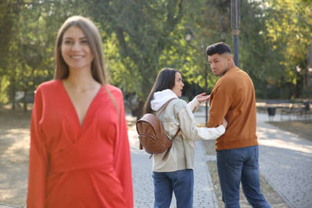 Disloyal man looking at another woman while walking with his girlfriend in park