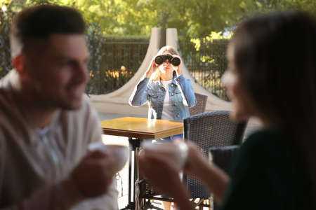 Jealous ex girlfriend spying on couple in outdoor cafe